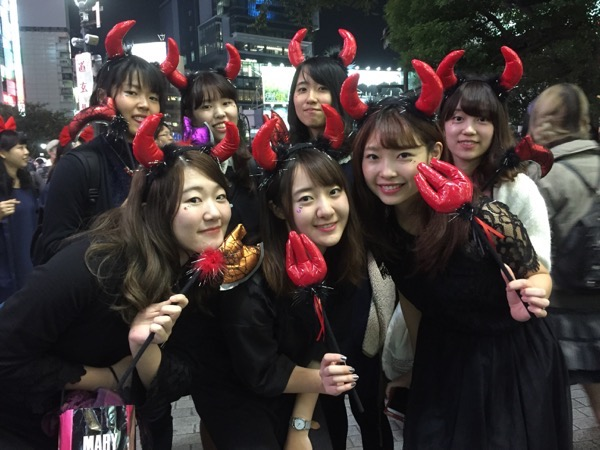 Girls posing in Halloween costumes with devil horns Shibuya Tokyo Japan